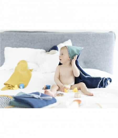 Cape de bain bébé personnalisée made in France avec bébé sur lit - fleurs bleues